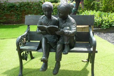 sculpture of two children sitting and reading on a garden bench