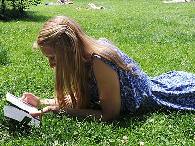 white woman lying in the grass reading
