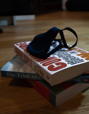 a pile of books with a mask